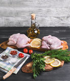 Two raw chicken carcasses. Cherry tomatoes, dill, parsley, pepper, salt crystal, cutting board, bottle of olive oil on a wooden background in rustic style Royalty Free Stock Photo