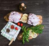 Two raw chicken carcasses. Cherry tomatoes, dill, parsley, pepper, salt crystal, cutting board, bottle of olive oil on a wooden background in rustic style, top Royalty Free Stock Photography