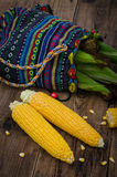 Two raw corn without leaves and bag of corn Stock Image