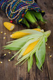 Two raw corn and small piece with bag of corn on dark wood table Royalty Free Stock Photos