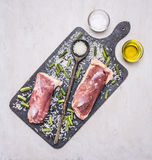 Two raw duck breast on a cutting board with a wooden spoon, wild rice, oil and salt wooden rustic background top view close up Royalty Free Stock Photo