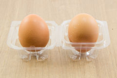 Two raw eggs in plastic box on wood board Royalty Free Stock Photos