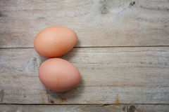 Two raw eggs on wood table. Two raw eggs on a wood table Stock Photo