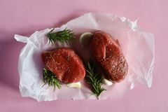 Two Eye Fillet Beef Steaks with Rosemary and Garlic on Pale Pink Background royalty free stock images