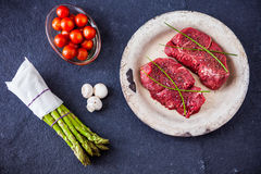 Two raw filet steaks with green asparagus, mushrooms. Cherry tomatoes with a slate background Stock Image