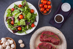 Two raw filet steaks with a green salad, cherry tomatoes Stock Photo