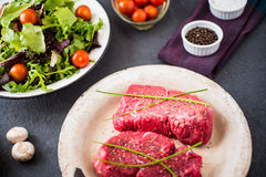 Two raw filet steaks with a green salad and cherry tomatoes. On a slate background Stock Image