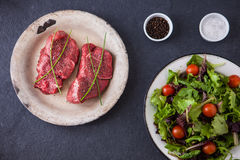 Two raw filet steaks with a green salad and cherry tomatoes. On a slate background Royalty Free Stock Photography