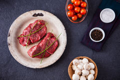 Two raw filet steaks with mushrooms, cherry tomatoes. Salt and pepper on a slate background Royalty Free Stock Images