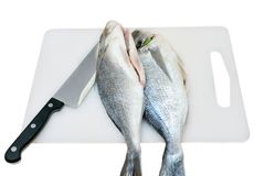Two raw fish on a cutting board and knife isolated Royalty Free Stock Images