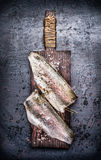 Two Raw fish fillet on old wooden cutting board on dark rustic background Stock Photos