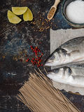 Two raw fish sea bass and other ingredients  on dark vintage background. Two raw fish sea bass and other ingredients - lime, buckwheat noodles, spices on dark Stock Photo