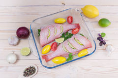 Two raw fishes of bass with lime. By tomatoes, onion, lemon, basil, by a garlic, parsley and spices stock photography