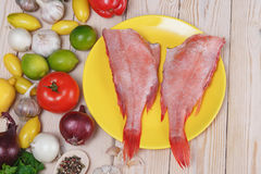 Two raw fishes of bass with lime. By tomatoes, pepper, onion, lemon, basil, by a garlic, parsley and spices stock photos