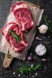 Two raw fresh marbled meat black angus steak ribeye, garlic, salt. On dark background royalty free stock photography