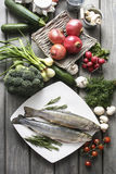 Two raw, fresh rainbow trouts among vegetables. Royalty Free Stock Photo