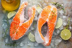 Two raw fresh salmon or trout steaks on ice, rich in omega-3 oil, with lime, thyme and olive oil on a blue rusty background. Healthy and dietary food. Top view royalty free stock photography