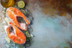 Two raw fresh salmon or trout steaks on ice, rich in omega-3 oil, with lime, thyme and olive oil on a blue rusty background. Healthy and dietary food. Top view stock image