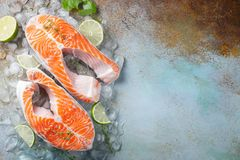 Two raw fresh salmon or trout steaks on ice, rich in omega-3 oil, with lime, thyme and olive oil on a blue rusty. Background. Healthy and dietary food. Top view royalty free stock photo