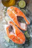 Two raw fresh salmon or trout steaks on ice, rich in omega-3 oil, with lime, thyme and olive oil on a blue rusty background. Healthy and dietary food. Top view royalty free stock images