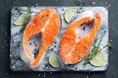 Two raw fresh salmon or trout steaks on ice, rich in omega-3 oil, with lime, thyme and olive oil on a dark background. Healthy and. Dietary food. Top view. Flat stock image