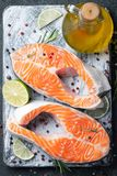 Two raw fresh salmon or trout steaks on ice, rich in omega-3 oil, with lime, thyme and olive oil on a dark background. Healthy and. Dietary food. Top view. Flat royalty free stock photography
