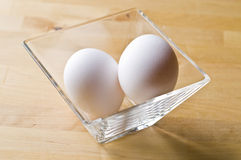 Two raw fresh white eggs in bowl. Over wooden background Stock Image