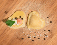 Two raw handmade ravioli ,open and closed,in the shape of heart,covered with flour and placed on wooden table Royalty Free Stock Image