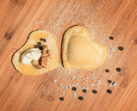 Two raw homemade ravioli,open and closed,in the shape of heart,covered with flour and placed on wooden table. Royalty Free Stock Image