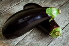 Two raw organic eggplant on old wooden background Stock Photos
