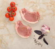 Two raw pork chops on a marble table. With cherry tomatoes, Basil and spices. top view Royalty Free Stock Photo