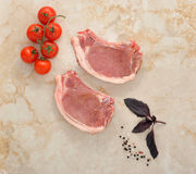 Two raw pork chops on a marble table. With cherry tomatoes, Basil and spices. top view Royalty Free Stock Photos