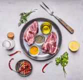 Two raw pork steaks in the pan with lemon, butter, pepper, salt and herbs wooden rustic background top view Royalty Free Stock Photos