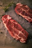 Two raw pork steaks with rosemary and pepper seeds on paper sheet. Vertical photo of two slices of pork neck steaks. The meat portions with red color and fat is stock photo