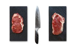 Rib eye steaks with knife on slate isolated. Two raw rib eye steaks on slate with knife isolated on white background. Cooking ingredients for restaurant dish Stock Photo