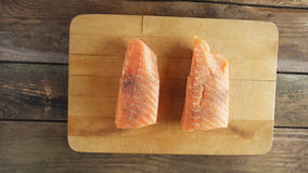 Two raw salmon fillets on wooden cutting board. Two raw salmon fillets on cutting board over wooden background Royalty Free Stock Image
