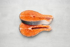 Two raw salmon fish steaks on stone background. Top view. stock image