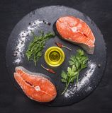 Two raw salmon steak on a stone cutting board with salt, pepper, herbs and butter and lined all around, top view. Two raw salmon steak on a stone cutting board Royalty Free Stock Photography