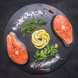 Two raw salmon steak on a stone cutting board with salt, pepper, herbs , lemon, lined all around, top view. Two raw salmon steak on a stone cutting board with Stock Photos