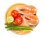 Two raw salmon steaks with tomatoes, lime  and green onion Stock Images