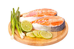 Two raw salmon steaks with lime and green onion on the cutting board Stock Photo
