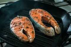 Two raw salmon steaks with spices and herbs on a grill pan. Clos. E up bbq grilled salmon steaks on black cast-iron ribbed frying pan. Healthy, fitness food Royalty Free Stock Photo