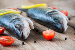 Two raw seabass fish with cherry tomatoes on a rustic wooden bac Stock Images