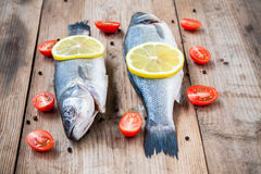 Two raw seabass fish with lemon and cherry tomatoes on wooden ba Stock Photo