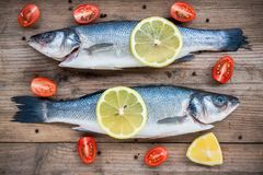 Two raw seabass fish with lemon and cherry tomatoes on wooden background Royalty Free Stock Photo