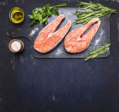 Two raw steak to salmon, seafood, healthy food with herbs, parsley, olive oil and salt dark vintage cutting board on wooden rus Stock Photos