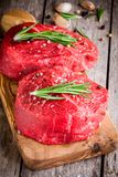 Two raw steaks with rosemary, garlic, salt and pepper royalty free stock photography