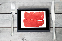 Two raw steaks on a tablet screen Royalty Free Stock Images