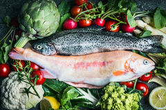 Two raw Trout fishes with fresh vegetables ingredients for healthy clean cooking Royalty Free Stock Photography