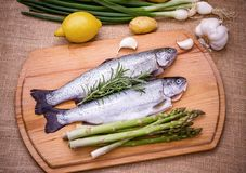 Two raw trout with green asparagus, lemon and garlic Stock Photo